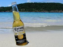 Bottle of Corona beer on a white sand beach with turquoise sea in background